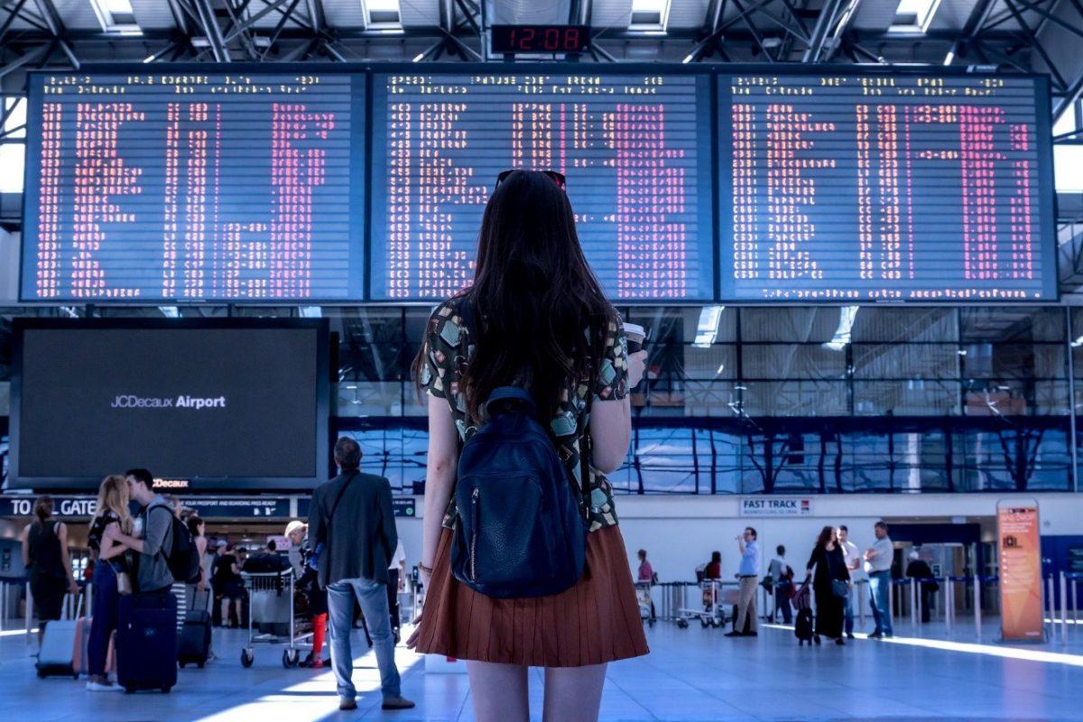 לימוד אנגלית לנסיעות בחורה בשדה תעופה בודקת לוח טיסות איילת צדוק