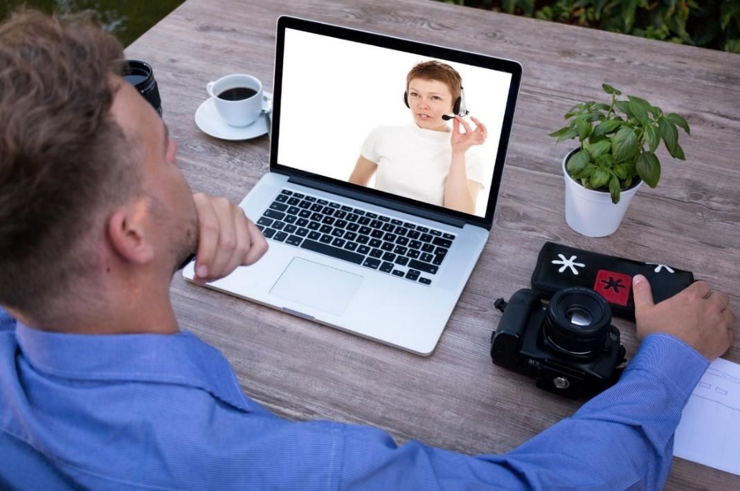ללמוד אנגלית באינטרנט גבר שטני יושב מול מחשב וצופה באישה המלמדת אנגלית איילת צדוק מורה לאנגלית